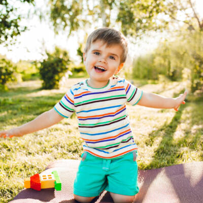 Little cute boy looks happy in summer garden with his toy house